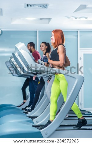 Warm-up run. Sport and slender girl running on a treadmill. Athlete dressed in sports uniforms and running in the gym . - stock photo