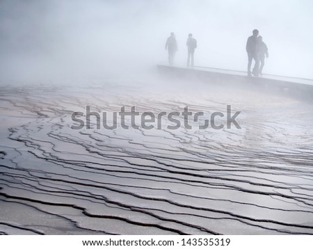 Warm, wet mist hovers over boardwalk, concealing shadowy figures and dropping moisture on bridge. Thermal pools in Yellowstone National Park - stock photo