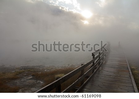 Warm, wet mist hovers over boardwalk, concealing shadowy figures and dropping moisture on bridge.  Thermal pools in Yellowstone National Park. - stock photo