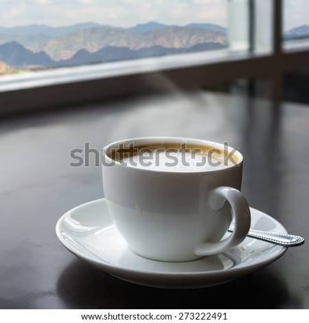 Warm white coffee cup on the table. With the backdrop of a beautiful landscape. - stock photo