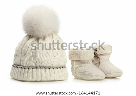 Warm woolen baby hat and booties over white - stock photo