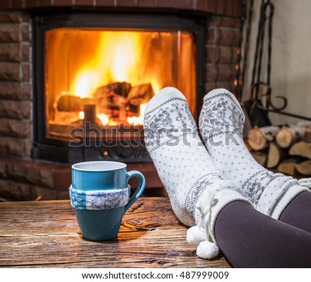 Warming and relaxing near fireplace. Woman feet near the cup of hot drink in front of fire.