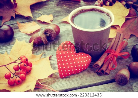 warming coffee cup, red heart and autumn still life on old table - stock photo