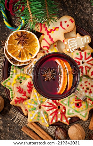 Warming mulled wine, spices and gingerbread cookie on a wooden background in rustic style