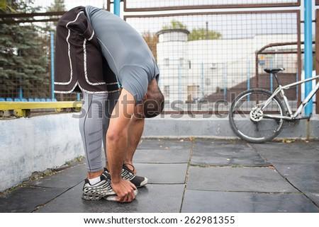 Warming-up.Athlete doing exercises at stadium - stock photo