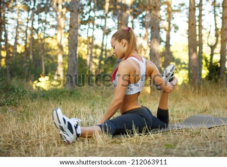 Warming-up.Beautiful young caucasian woman in fitness wear doing exercises in a park