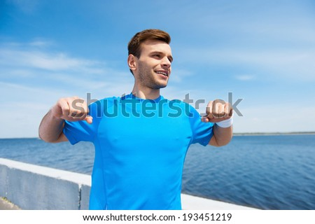 Warming up before running. Handsome young man exercising while standing outdoors  - stock photo