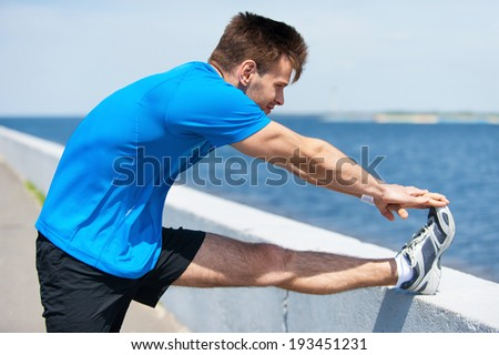 Warming up. Handsome young man doing stretching exercises while standing outdoors  - stock photo