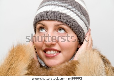 Warming Up. Young woman wearing a wool scarf and knit hat. Fall/Winter time.