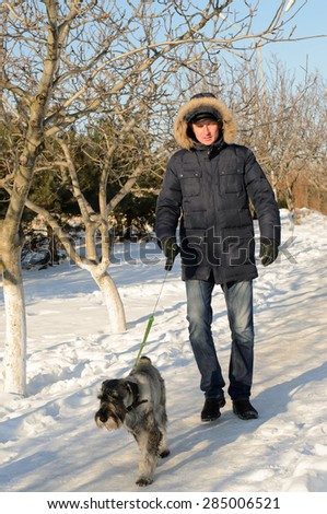 Warmly dressed man walking his dog on a lead in winter snow as they both enjoy the sunshine outdoors