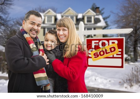 Warmly Dressed Young Mixed Race Family in Front of Sold Home For Sale Real Estate Sign and House with Snow On The Ground. - stock photo