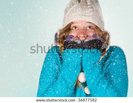 Warmly tucked in young woman in winter with snow - stock photo