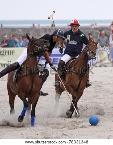 """WARNEMÜNDE, GERMANY - MAY 22: Hugo Iturraspe  and Comanche Gallardo compete in  the semifinal of  """"1. Beach Polo Baltic Cup Warnemünde"""" at the beach of Warnemünde, Germany on May 22, 2011, - stock photo"""