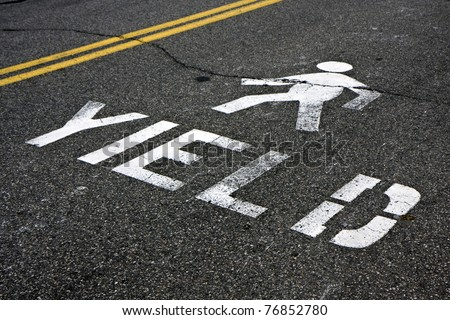 Warning at crossroad saying yield and person sign on asphalt - stock photo