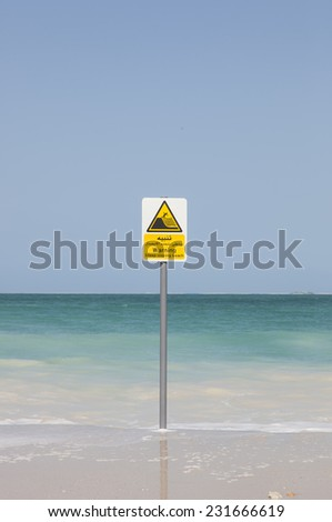 warning board on public beach dubai - stock photo