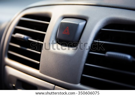 warning button in a car. modern car dashboard to activate hazard lights - stock photo