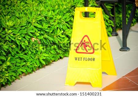 "warning label ""Wet floor"" yellow on the tile floor - stock photo"