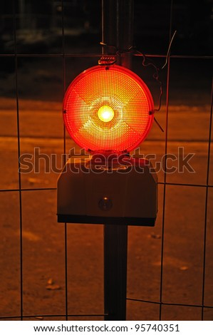 Warning light  Photo of a burning warning light in front of metal grid fence - stock photo