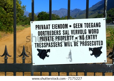 Warning message at the gate (English and Afrikaans) - and mountains as a background. Shot in Stellenbosch Mountain, Western Cape, South Africa. - stock photo