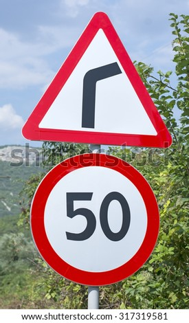 Warning road sign on mountain highway - stock photo