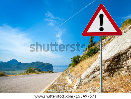 Warning road sign with an exclamation mark in red triangle on mountain highway - stock photo