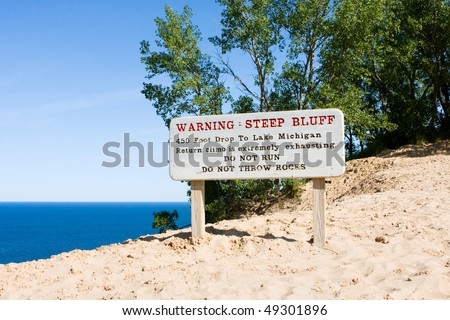 Warning sign about the steep bluff at Sleeping Bear Dunes National Lakeshore on Lake Michigan - stock photo