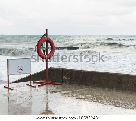 Warning sign and a life buoy on the waterfront in the storm. - stock photo