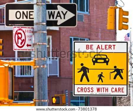 Warning sign at a dangerous, confusing and busy cross-walk. - stock photo