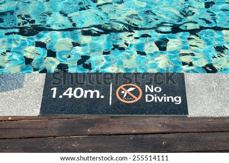warning sign at edge of swimming pool - stock photo