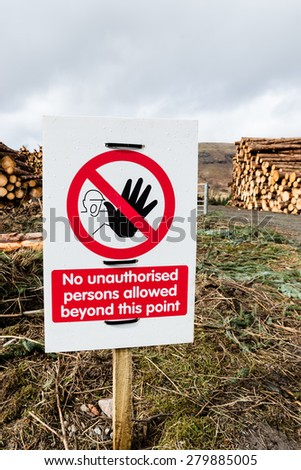 Warning sign at location of a stack of harvested logs awaiting collection. - stock photo