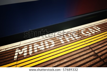 Warning sign at Tube station and motion blured train in London. - stock photo
