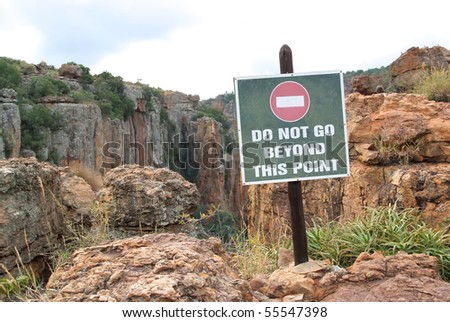 "Warning sign: ""Do not go beyond this point"" at a cliff."