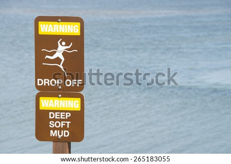 Warning Sign for  drop off, deep soft mud potential for drowning. - stock photo