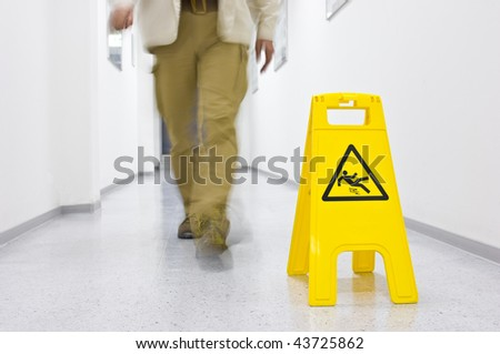 Warning sign for slippery floor, person walking down the floor - stock photo