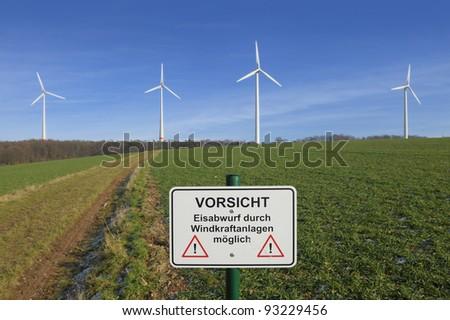 Warning sign in wind turbine park - stock photo