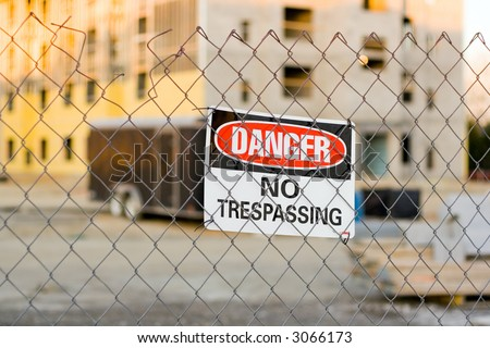 Warning Sign on a Fence Around a Construction Site - stock photo