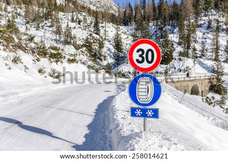 Warning Sign on a Mountain Road in Winter - stock photo