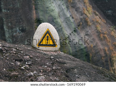 warning sign on a rock at the edge of the abyss - stock photo