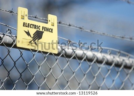 Warning sign on an electric fence on an industrial facility - stock photo