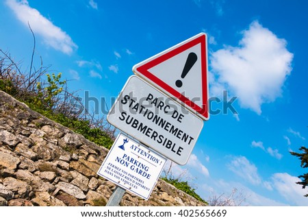 warning sign on Noirmoutier, France slipway for parking one side only and liable to flooding - stock photo