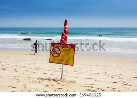 Warning sign on the beach swimming prohibited is disregarded by a man - stock photo
