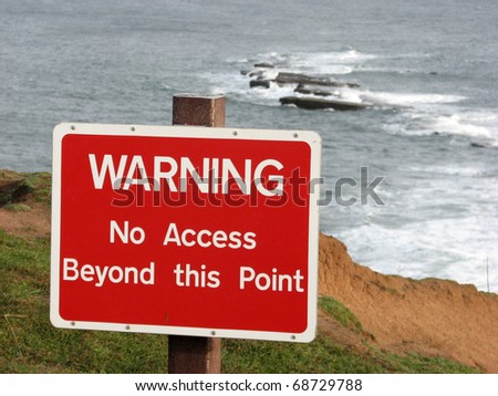 Warning sign on top of cliff edge at Filey Brigg - stock photo