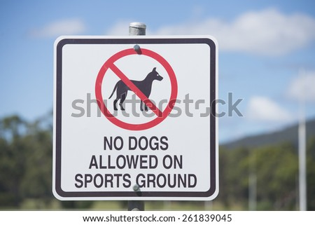 Warning sign outdoor No Dogs Allowed, prohibited, have restricted access on or to Sports Ground or exercise oval, blurred background. - stock photo