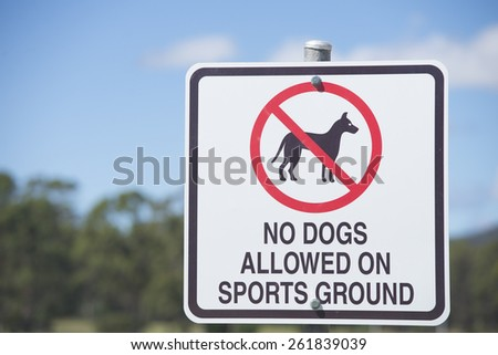 Warning sign outdoor No Dogs Allowed, prohibited on, have restricted access to Sports Ground or exercise oval, blurred background, copy space. - stock photo
