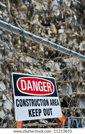 warning sign posted on fence around massive demolition project, shallow depth of field - part of series - stock photo