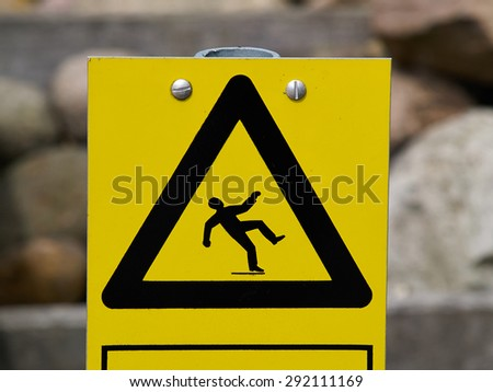 Warning sign slippery floor surface outdoors on a wooden deck - stock photo