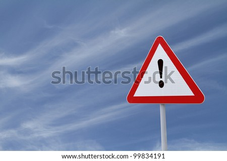 Warning sign with exclamation point with a blue sky background - stock photo