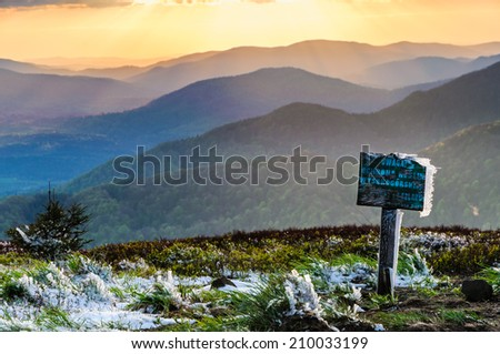 Warning signpost with last sun rays after fresh snow fall in Bieszczady national park, Poland - stock photo