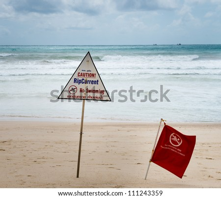 Warning signs about rip current at a beach with storm clouds on background - stock photo