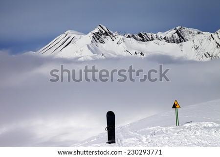Warning sing, snowboard on off-piste and mountains in fog. Caucasus Mountains, Georgia, ski resort Gudauri. - stock photo